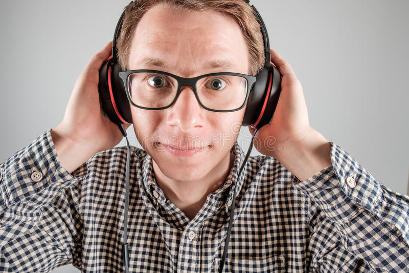Man listening to music. Cheerful guy enjoying loud music holding them tightly to ears isolated on gray background royalty free stock images