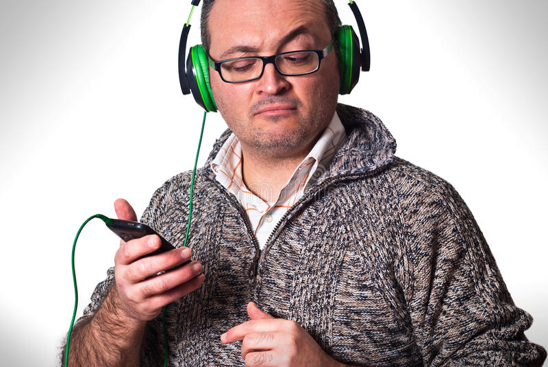 Download Man Listening To Music And Looking At Cell Phone Stock Photo - Image: 38424544