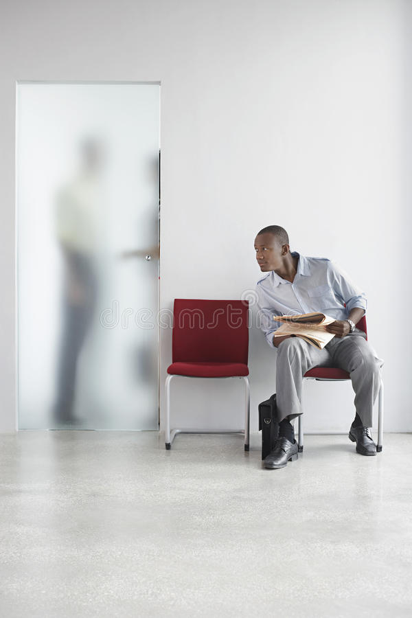 Man Listening To People Talk Behind Translucent Door royalty free stock photography