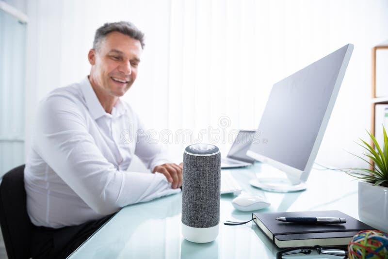Man Listening To Wireless Speaker In Office. Smiling Mature Man Listening To Music On Wireless Speaker stock photos