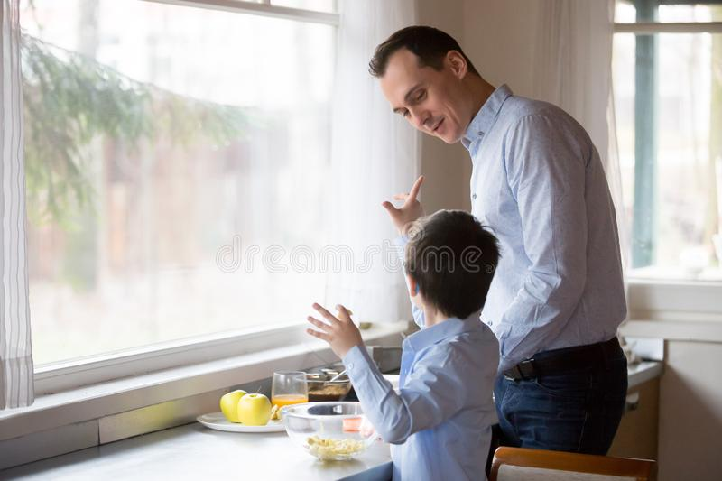 Father with son cooking together in the kitchen royalty free stock photography