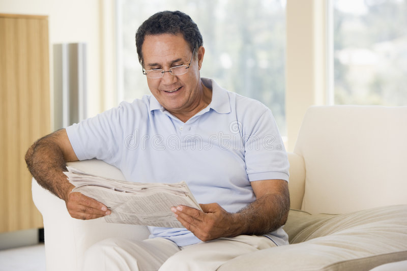 Man in living room reading newspaper smiling. Man in living room sitting down reading a newspaper smiling royalty free stock images