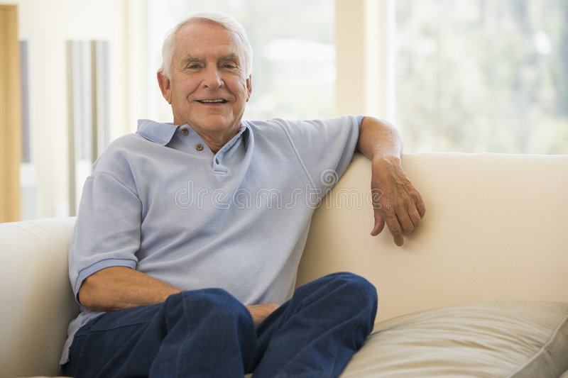 Man in living room smiling royalty free stock photo