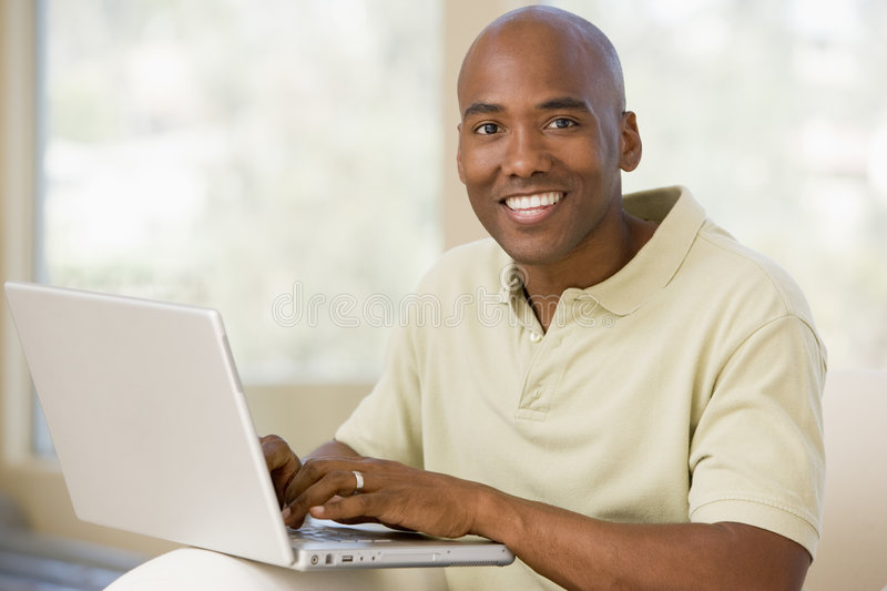 Download Man In Living Room Using Laptop And Smiling Stock Photo - Image: 5928346