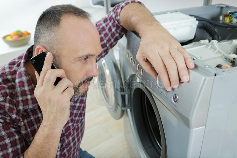 Man loading clothes into washing machine in kitchen. Man stock image