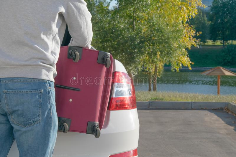 A man loads in the trunk of a car, a red suitcase, on one coast, in the fall royalty free stock photography