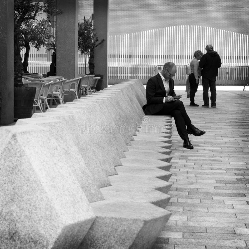 A man in London, England. A man in a suit looking at his phone while sitting on a concrete bench in London, England stock photos