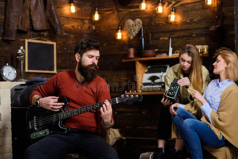 Man with long beard enjoying music. Musician with calm, concentrated face playing for his wife and daughter. Mom helping royalty free stock photo