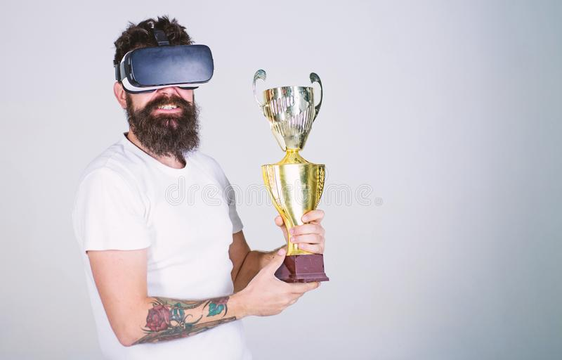 Man with long beard happy about his victory in online games tournament, gaming concept. Cheerful bearded champion. Holding golden cup. Nerdy bearded man in VR stock image