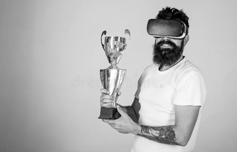 Man with long beard happy about his victory in online games tournament, gaming concept. Cheerful bearded champion. Holding golden cup. Nerdy bearded man in VR royalty free stock photo