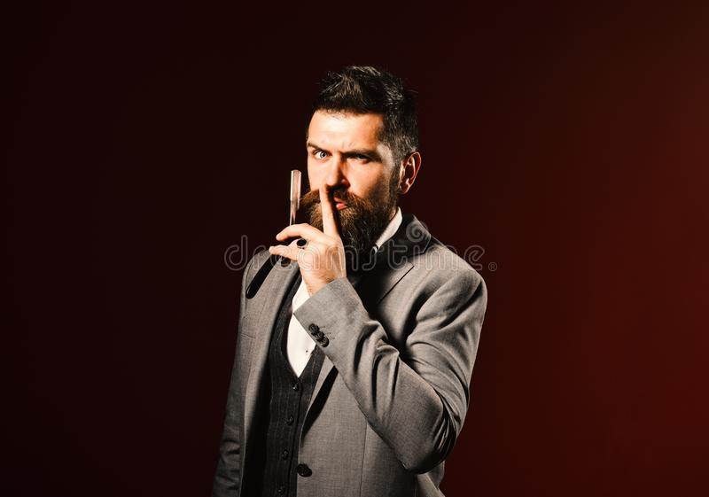 Man with long beard holds blade for razor. Barbershop advertising. Concept. Businessman with secret face on dark red background. Macho in formal suit shows royalty free stock photo