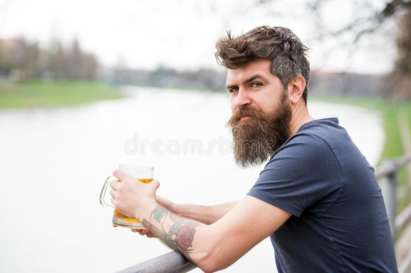 Man with long beard looks relaxed. Man with beard and mustache on calm face, river background, defocused. Bearded man. Holds beer mug, drinks beer outdoor royalty free stock images