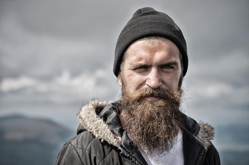 Man with long beard and mustache wears hat. Hipster on strict face with beard looks brutally while hiking. Masculinity royalty free stock image