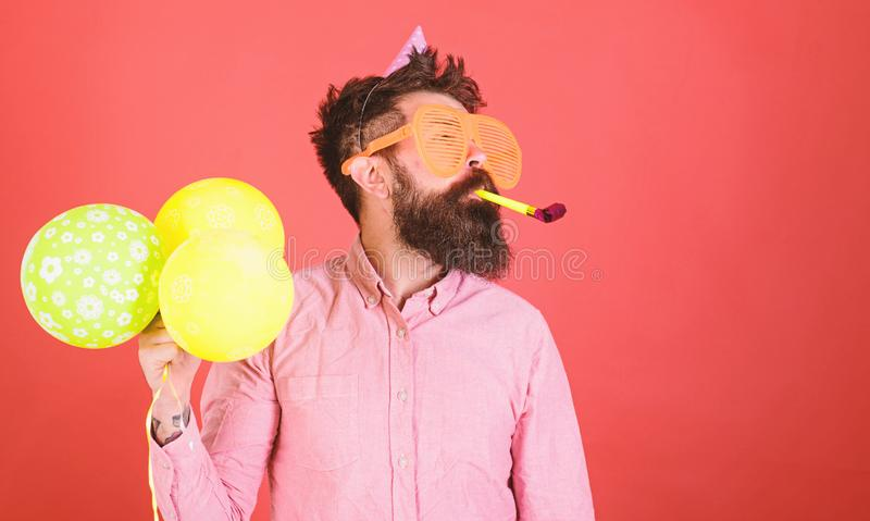 Man with long beard on red background. Bearded man in huge glasses with party whistle, celebration concept. Crazy man. With trimmed beard having fun. Perfomer stock images
