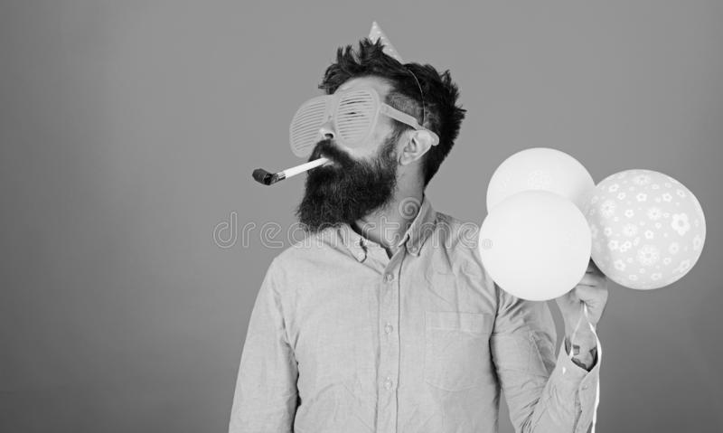 Man with long beard on red background. Bearded man in huge glasses with party whistle, celebration concept. Crazy man. With trimmed beard having fun. Perfomer royalty free stock photo