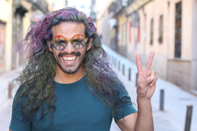 Man with long colourful hairstyle giving peace sign royalty free stock photography