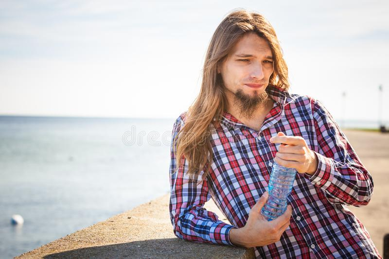 Man long hair relaxing by seaside drinking water stock images