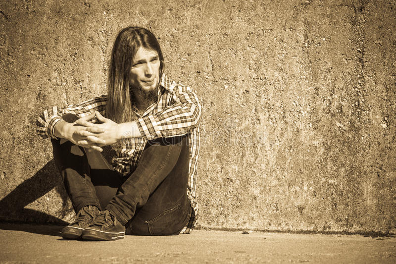 Man long haired sitting alone sad on grunge wall. Man bearded long hair sitting sad alone by grunge wall outdoor. Unemployment depression or sadness concept royalty free stock image
