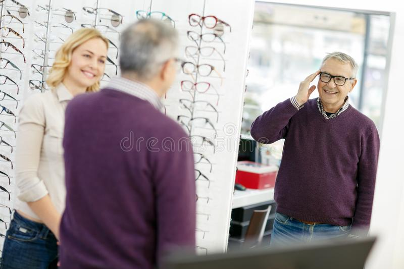 Man look in mirror model of frame glasses. Senior men look in mirror new model of frame glasses royalty free stock photos