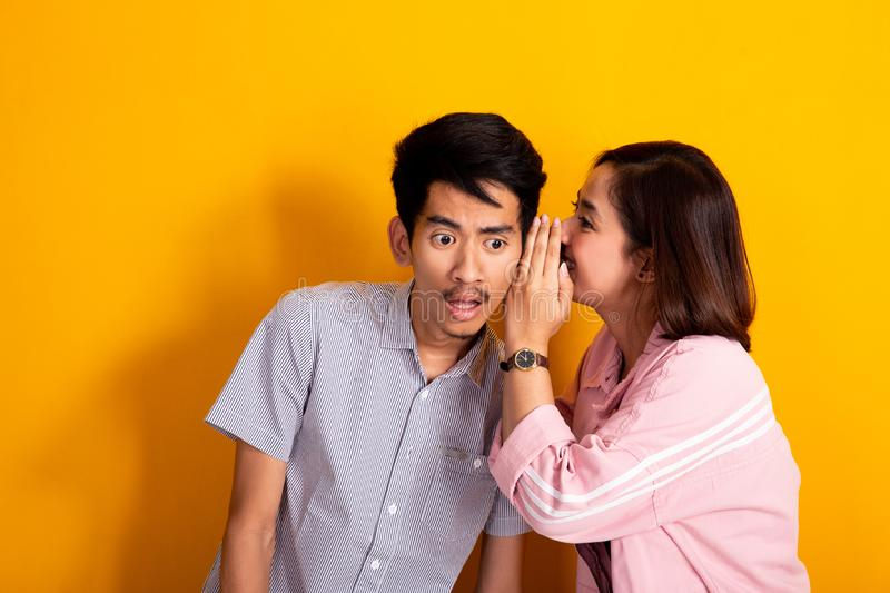 Man looked shocked while woman whispering to his ear. Woman whispering to a men about gossip, men looked shocked shoot over yellow background stock photo