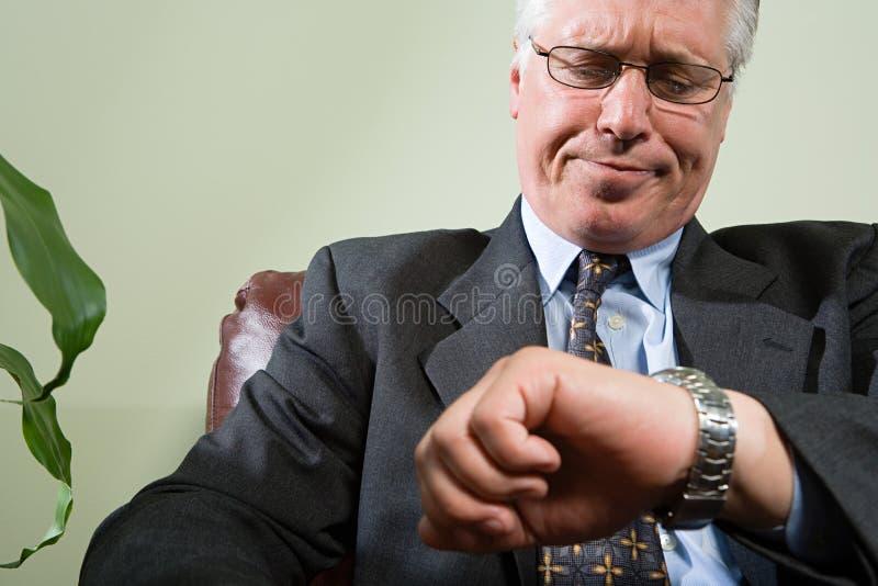 Man looking anxiously at watch royalty free stock photo