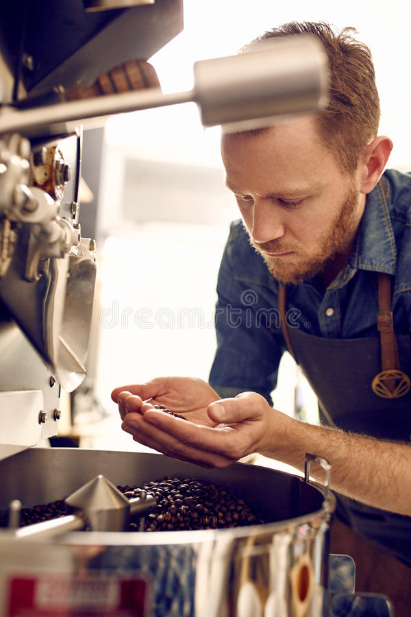 Free Man Looking At Roasted Coffee Beans From A Roasting Machine Stock Photos - 65618353