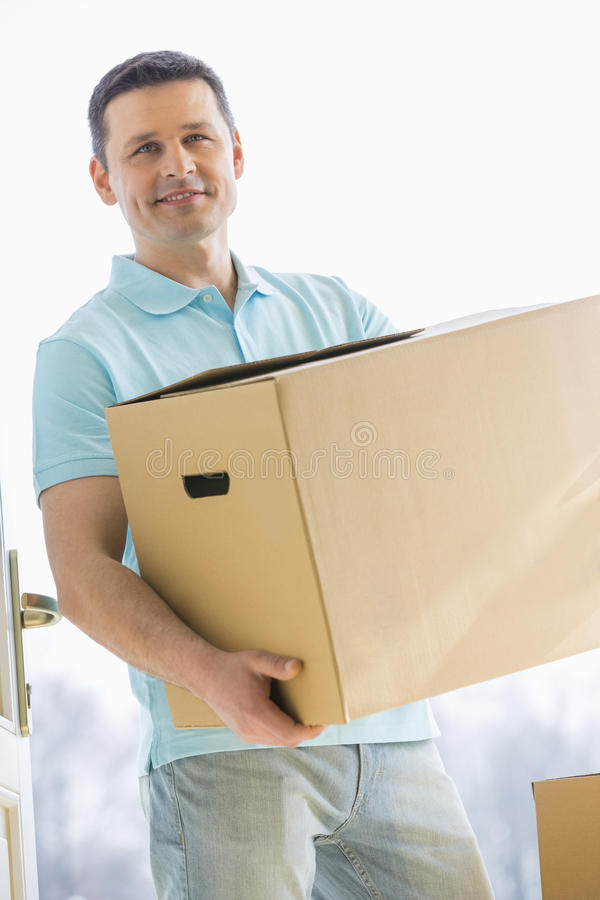 Man looking away while carrying cardboard box while entering new house stock image