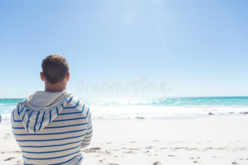 Man looking at the beach. Rear view of a Caucasian man standing on the beach with blue sky and sea in the background, looking away royalty free stock images