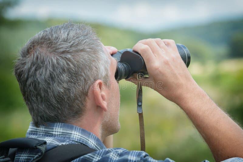 Man looking through binocular royalty free stock photo