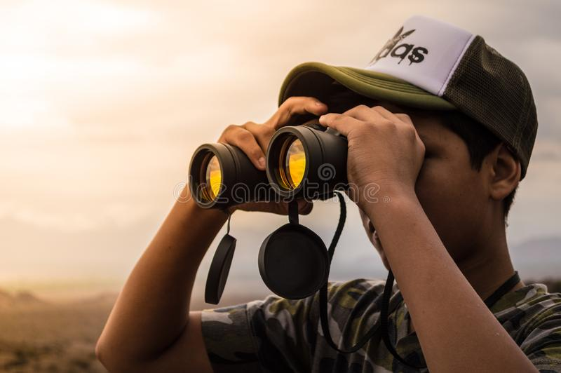 Man Looking in Binoculars during Sunset royalty free stock images