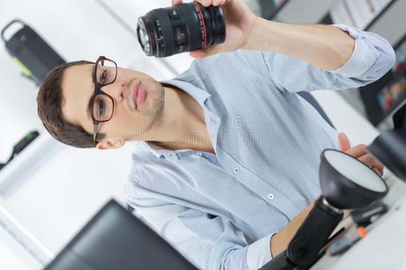 Man looking at broken photographic lense stock photography