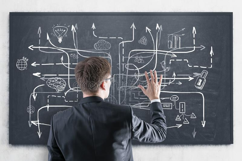 Man looking at business plan at blackboard. Rear view of young businessman in suit and glasses looking at blackboard with business plan sketch drawn on it royalty free stock images