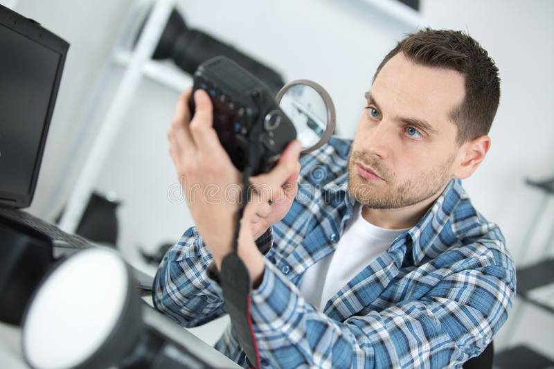 Man looking at camera body with magnifying glass royalty free stock image