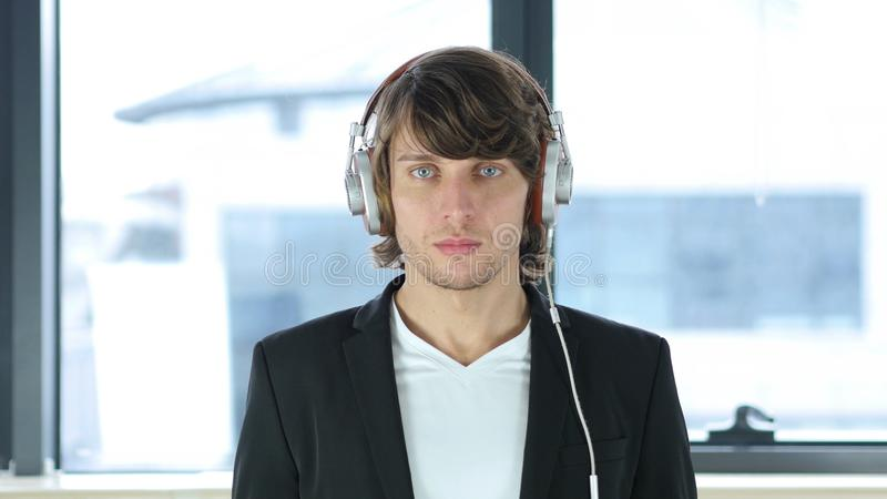 Man Looking in Camera with Headphones on His Head royalty free stock photo