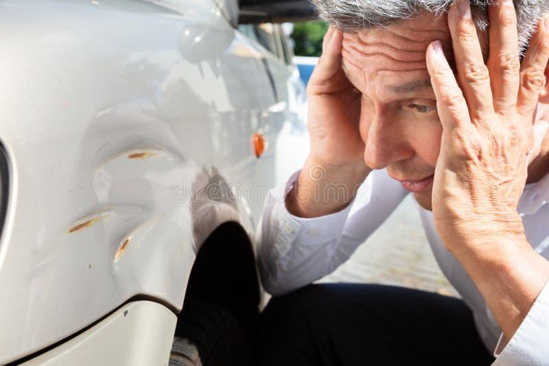 Man Looking At Damaged Car. Close-up Of A Mature Man Looking At Damaged Car royalty free stock photo