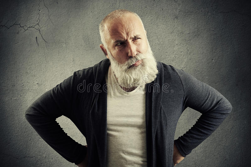 Man looking with distrust at something. Senior man looking with distrust at something over dark grey wall royalty free stock images