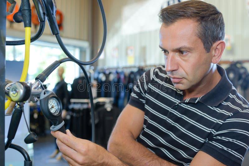 Man looking at diving apparatus stock photography