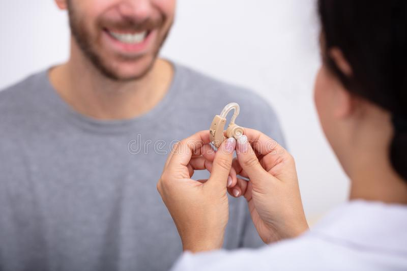 Man Looking At Doctor Holding Hearing Aid. Young Male Patient Looking At Female Doctor Holding Hearing Aid In Clinic royalty free stock images