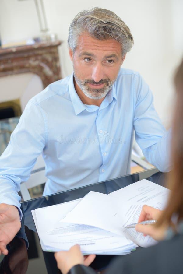 Man looking doubtfully at lady passing him paperwork. Man royalty free stock photos