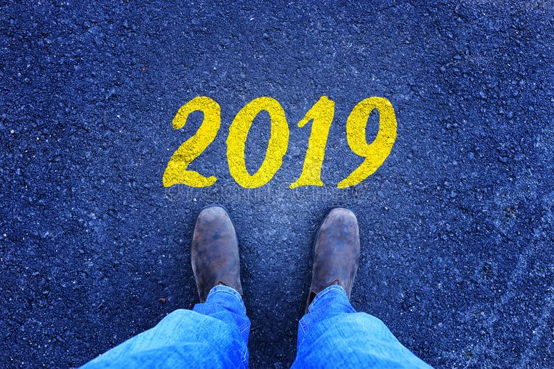Man looking down at his feet on Asphalt road with 2019 number painted on it. stock images