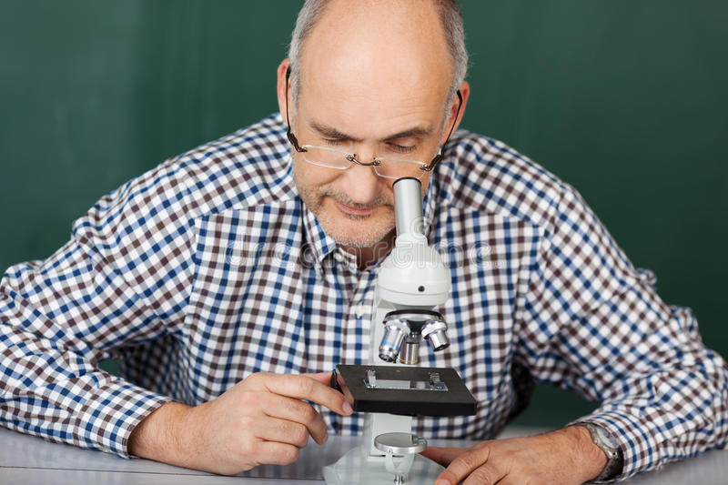 Man looking down a microscope royalty free stock photos