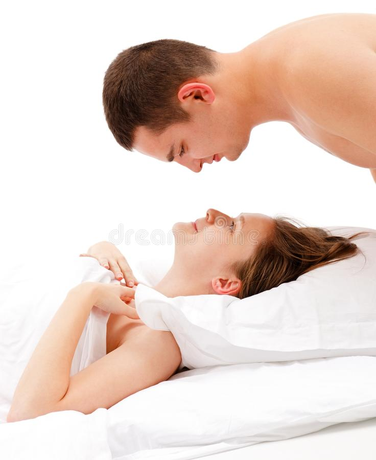 Man looking down on woman laying in bed royalty free stock photo