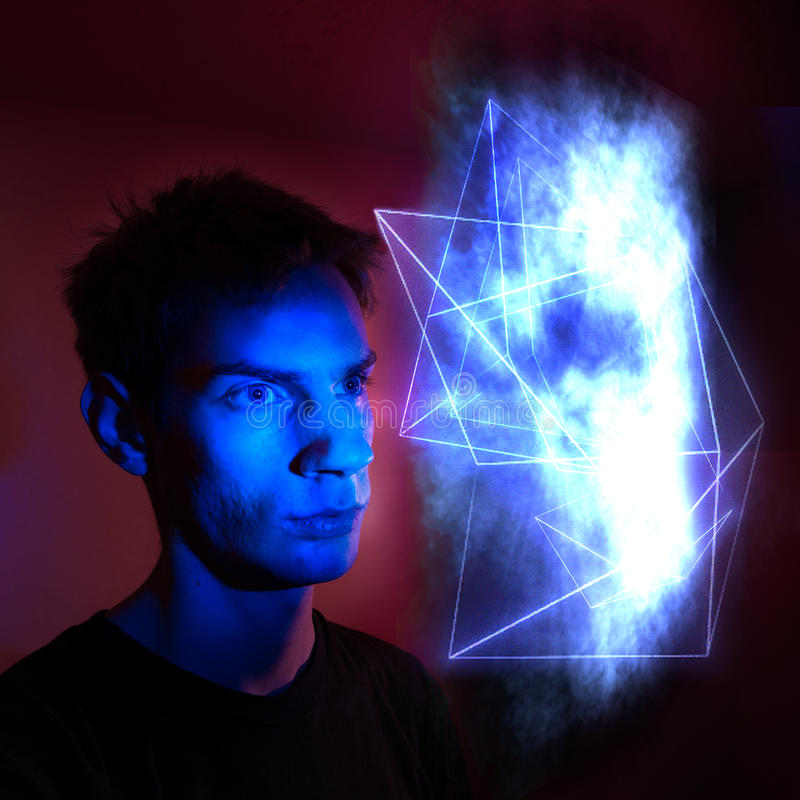 Man looking at energy source. Portrait of young man staring at abstract blue energy source with geometric lines royalty free stock photo