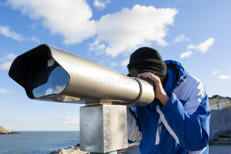 Man looking forward by telescope stock images