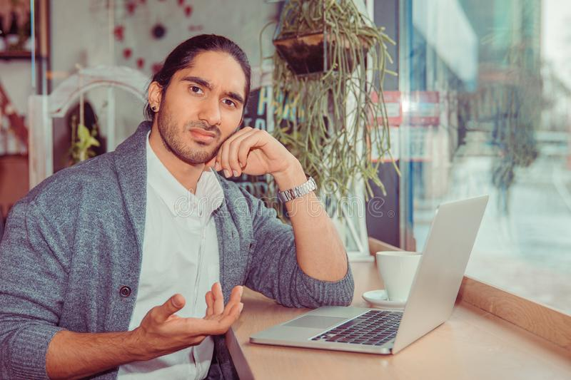 Man looking frustrated hand gesture in front of the computer. Man looking at you camera frustrated hand gesture in front of the computer. Closeup portrait of a royalty free stock images