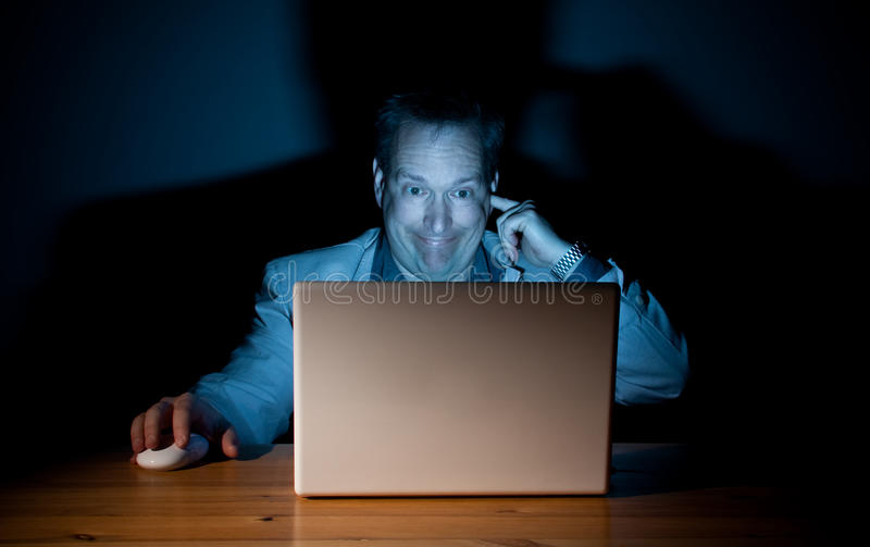 Goofy computer guy. Man looking goofy in front of his computer royalty free stock images