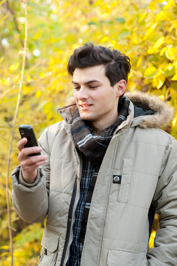 Man looking on his cellphone in autumn park. Young smiling man looking on his cellphone in autumn park stock image