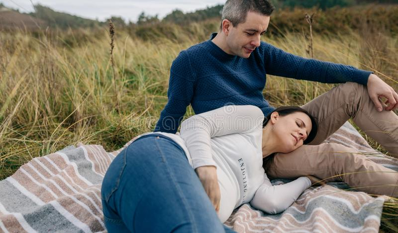 Man looking his pregnant woman resting on the grass royalty free stock images