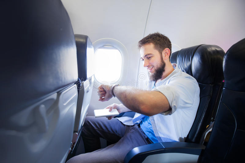 Man looking at his smart watch in airplane stock photo