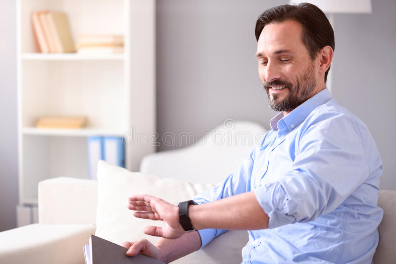 Man looking at his smartwatch. What time is it. Smiling middle-aged man looking at his smartwatch while sitting on the sofa with a book royalty free stock photo